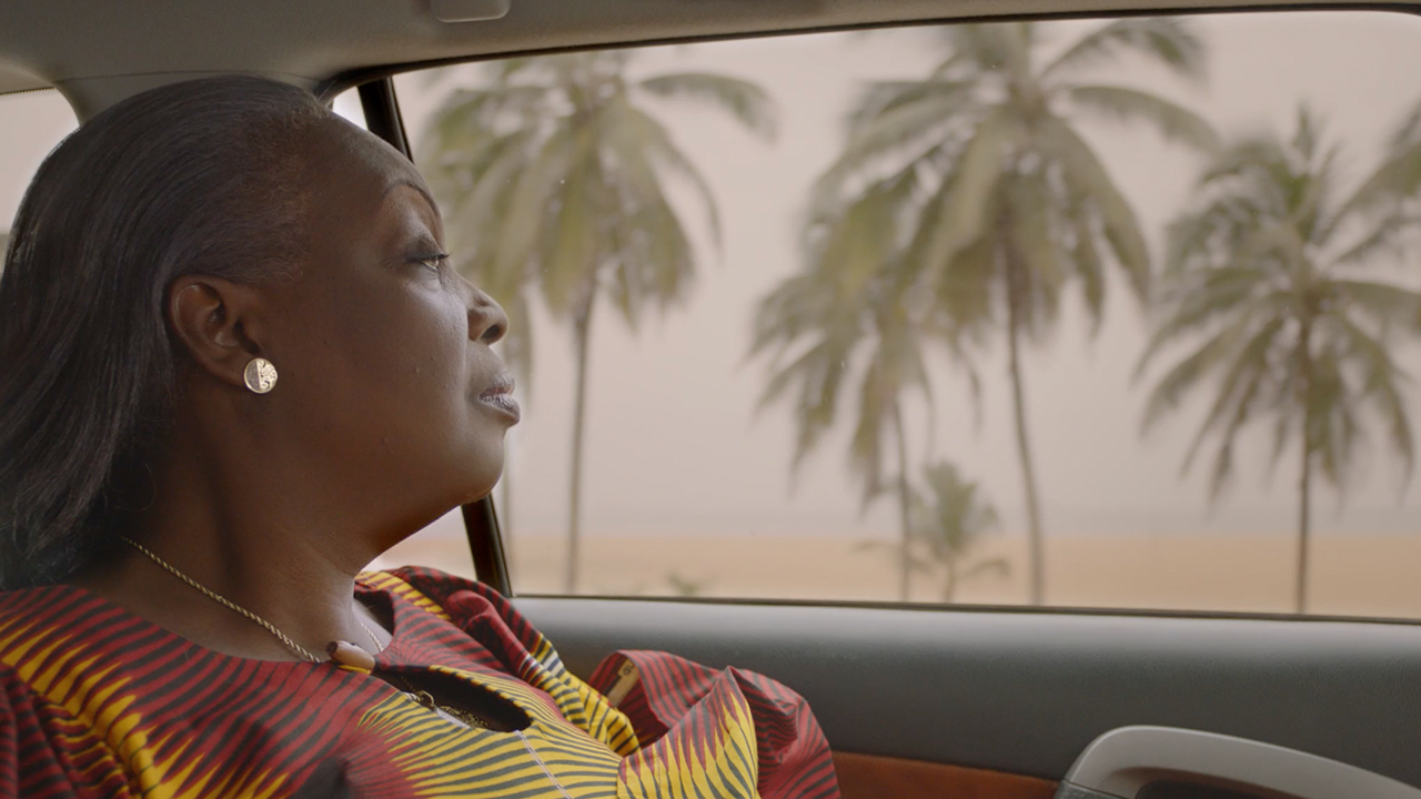 African woman in car wearing Vlisco