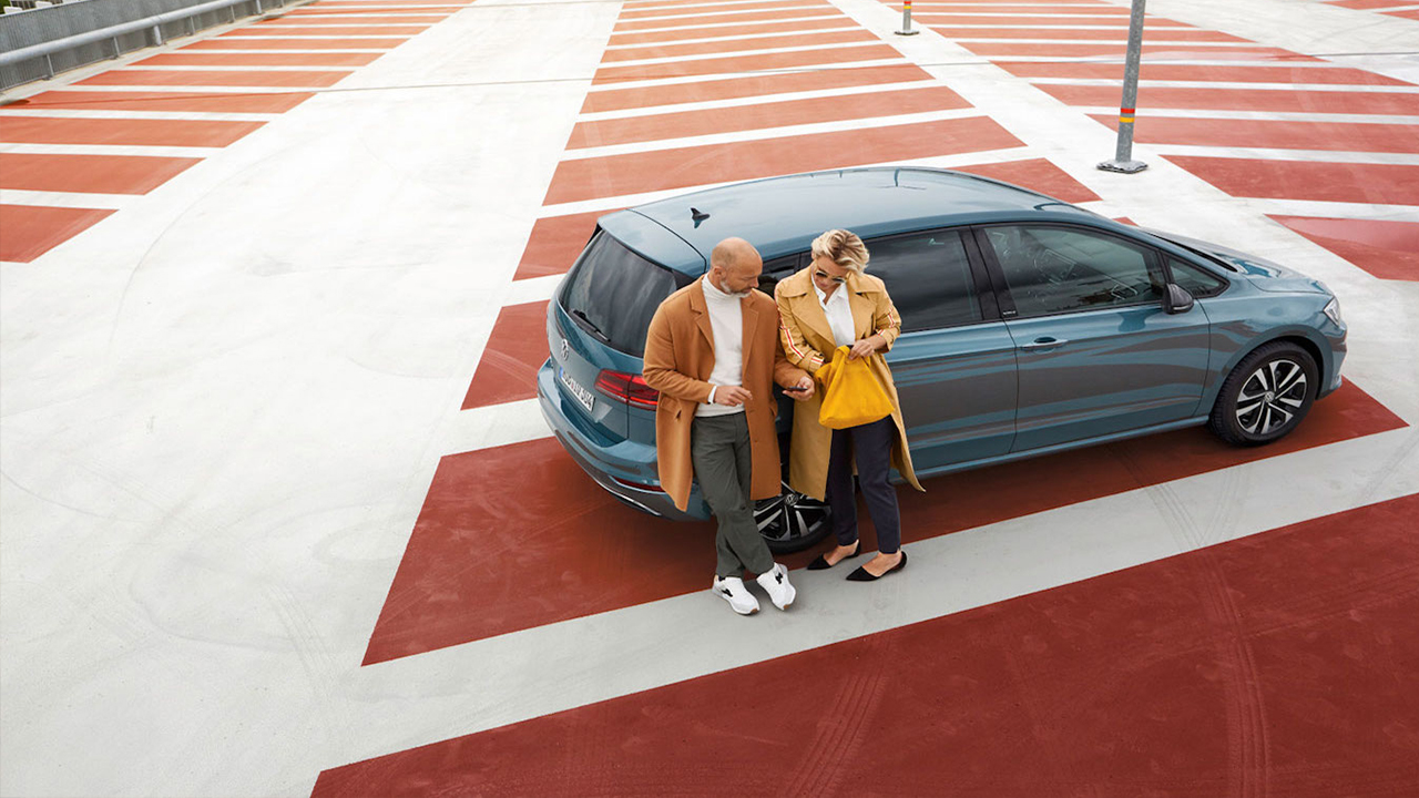Couple on parking with Volkswagen IQ